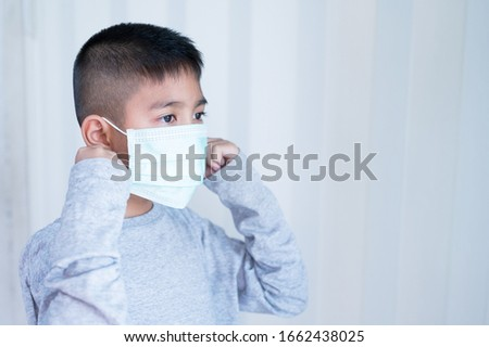Portrait Asian kid wearing medical mask.A boy wearing mouth mask against air smog pollution. Concept of corona virus quarantine or covid-19.Protection against virus and infection control concept. #1662438025