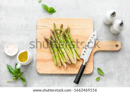 Asparagus cooking concept, top down view on a cutting board with fresh bunch of asparagus, lying down on a kitchen table, spring healthy cooking idea #1662469156