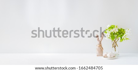 Home interior with easter decor. Spring flowers in a vases, easter eggs on a light background #1662484705
