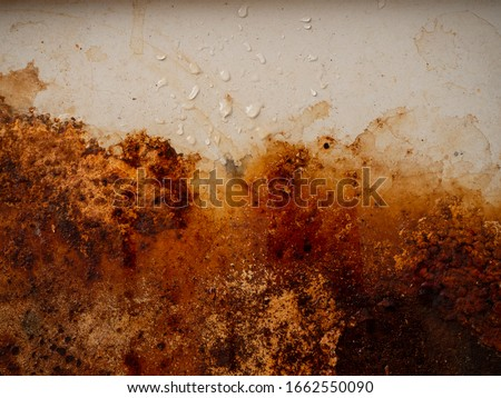 Brown, black and yellow wet rust on white enamel with smudges of water and drops. Rusted brown and white abstract texture. Corroded white metal background. Rusted white painted metal wall. #1662550090