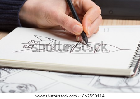 Artist drawing an anime comic book in a studio. Wooden desk, natural light. Creativity and inspiration concept. #1662550114