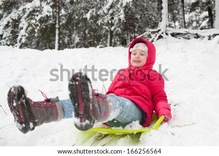 Kid sliding with sledge in the snow