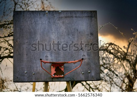 rusty old basketball hoop against a sky in the evening