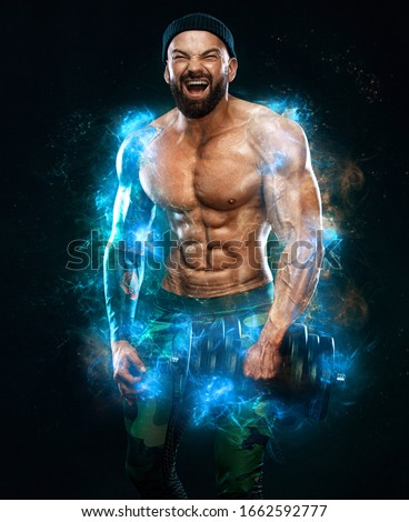 Man athlete bodybuilder. Muscular young fitness sports guy doing workout with dumbbell in fitness gym. Energy and power. #1662592777