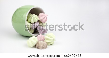 Marshmallow multicolored. Meringue marshmallows in a green cup on a light background. Colorful meringues on a white background. Lots of sweet marshmallows. Marshmallow drops from a cup. copyspace #1662607645