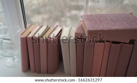 Large stack of books on windowsill. Books wrapped in colored paper lie on window sill. #1662631297