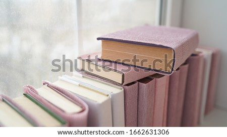 Large stack of books on windowsill. Books wrapped in colored paper lie on window sill. #1662631306