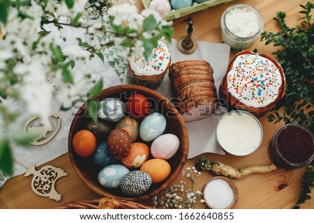 Easter food flat lay. Easter eggs natural dyed, easter bread, ham, beets, butter, green branches and flowers on rustic wooden table. Traditional Easter Food for breakfast #1662640855