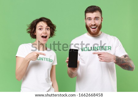 Excited two friends couple in volunteer t-shirt isolated on green background. Voluntary free work assistance help charity grace teamwork concept. Point fingers on mobile phone with blank empty screen