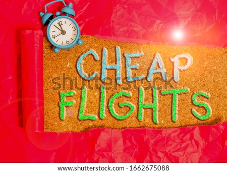 Text sign showing Cheap Flights. Conceptual photo costing little money or less than is usual or expected airfare Alarm clock and torn cardboard placed above a wooden classic table backdrop.