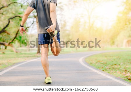 Back view of Asia man runner doing stretching exercise, warm up before for running in morning on track in the park  Royalty-Free Stock Photo #1662738568