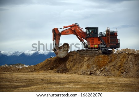 WESTPORT, NEW ZEALAND, JULY 12, 2013: A 190 ton digger loads a 130 ton truck with rock overburden at Stockton open cast coal mine on July 12, 2013 near Westport, New Zealand.  #166282070