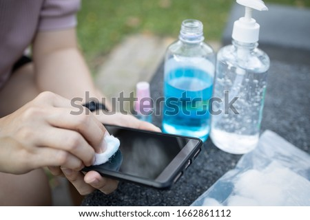 Cleaning mobile phone to eliminate germs,Covid-19 hands of asian woman cleaning the phone by hand sanitizer gel,girl using cotton wool with alcohol to wipe to avoid contaminating with Corona virus #1662861112