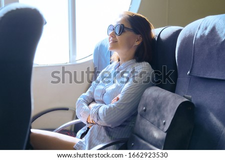 Passenger shipping, woman sitting in cabin of comfortable sea ferry, resting reading magazine drinking coffee, sea trips, tourism #1662923530