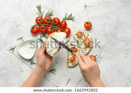 Woman making tasty sandwich with cream cheese on white background Royalty-Free Stock Photo #1662942802