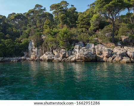 Quiet and peaceful place with emerald water with rocks on the shoreline, and trees behind #1662951286