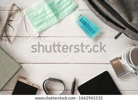Top view or flat lay of face mask ,sanitizer hand gel to protect against Coronavirus or COVID-19 and neccessary items for daily working life , Today's personal item  for health protection concept #1662965131