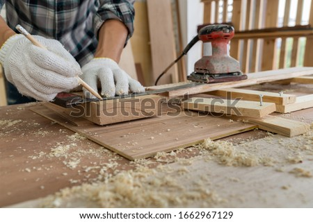 Carpenter working on wood craft at workshop to produce construction material or wooden furniture. The young Asian carpenter use professional tools for crafting. DIY maker and carpentry work concept. #1662967129