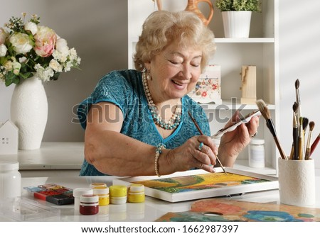 Adult senior woman paints a picture in her studio. Hand made art crafts theme
