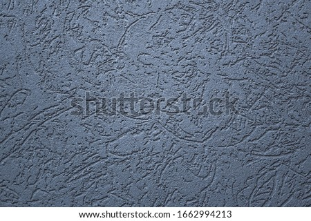 Texture of a grey stone decorative plaster or concrete wall. Abstract background for design. Gray decorative plaster inside the house. Royalty-Free Stock Photo #1662994213