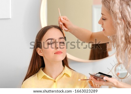 Professional makeup artist working with young woman in salon #1663023289