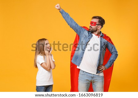 Bearded man in casual clothes Super hero costume have fun with cute child baby girl. Father little kid daughter isolated on yellow background. Love family parenthood childhood concept. Fly gesture arm