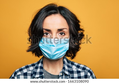 Young serious woman in a protective medical mask. Woman wearing face mask because of Air pollution or virus epidemic. #1663108090