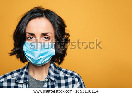 Young serious woman in a protective medical mask. Woman wearing face mask because of Air pollution or virus epidemic. #1663108114
