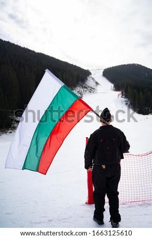 Bulgarian Man celebrating Day of Liberation in Bansko, Bulgaria Ski resort. National holiday, parade, people, women celebrating, laughing. Patriotic scene, snow mountain background #1663125610