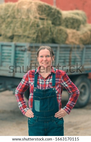 Female farmer posing in front of hay wagon. Portrait of woman farm worker in plaid shirt and bib overalls by the tractor trailer filled with dairy farm livestock feed hay bales. #1663170115