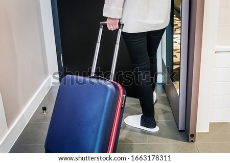 hotel visitor with a suitcase in the hotel room. Concept on the theme of arrival in the hotel room #1663178311