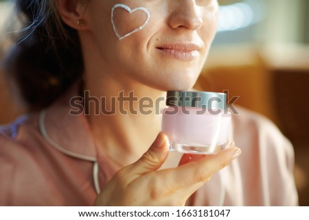Closeup on smiling stylish woman in pajamas with white facial cream heart on cheek holding pink cosmetic jar in the modern house in sunny winter day. #1663181047