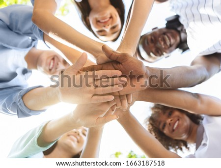 Student Friendship. Portrait of happy university friends stacking hands together, showing unity and togetherness, low angle view, selective focus Royalty-Free Stock Photo #1663187518