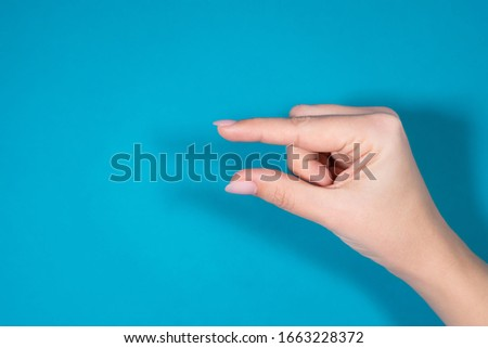 Closeup top view horizontal photography of female hand forming gesture Little bit. Empty space between two fingers of woman. Isolated on bright blue background. Royalty-Free Stock Photo #1663228372