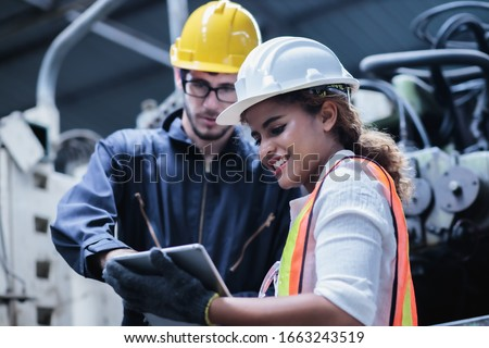 Two maintenance engineers men and women inspect relay protection system with laptop comp. They work a heavy industry manufacturing factory. #1663243519