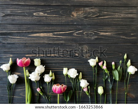 Fresh spring flowers pattern on dark wood background. Top view. Tulips, roses, carnations. Space for your text. Nature photography For your banner, greeting card. Rustic.