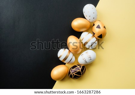 Golden, black, white easter eggs on a yellow-black background. Geometry. Minimal concept. View from above. Card with copy space for text.