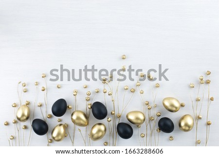 Minimal gold eggs easter concept. Stylish easter golden and black quail eggs with dried golden flax linum on white wooden background. Flat lay trendy easter. Happy easter card with copy space for text #1663288606