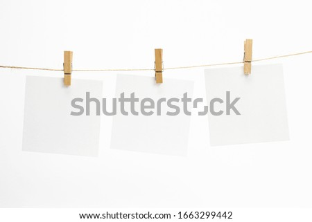 Empty paper sheets for notes, frames that hang on a rope with clothespins and isolated on white. Blank cards on rope. Mockup template for memories backdrop, photos, social media etc. #1663299442