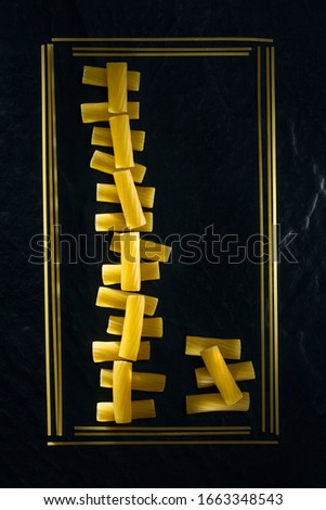 Uncooked pasta close-up. Abstract picture of pasta, vermicelli and spaghetti of different types in a frame on a black background. Copy space