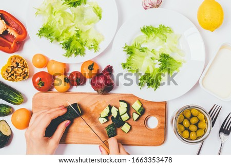 Cooking healthy food process. Top view of woman hands cut fresh cucumber on cutting board next to ingredients and plates for vegetable salad. #1663353478