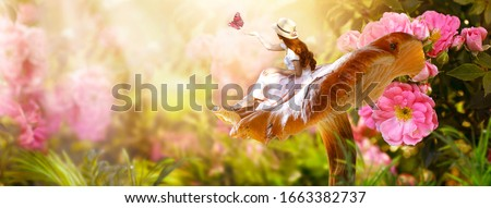 Elf woman in dress and hat sitting on fantasy giant large mushroom releasing butterfly from hand in magical enchanted fairy tale rose flower blooming garden, fairytale floral fabulous background
