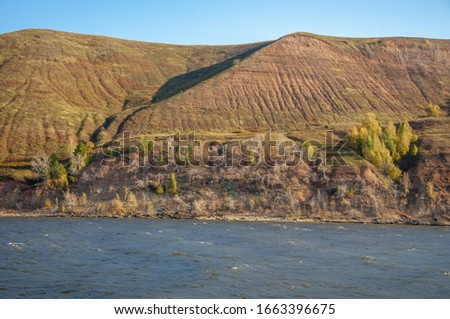 Autumn landscape, dark blue water, last warm days, river, trees, windy weather, yellow-red autumn leaves #1663396675