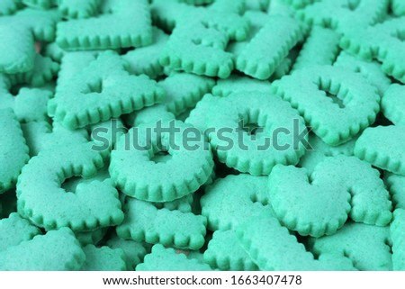 Closeup aqua blue alphabet cookies spelling the word GOOD on cookies pile #1663407478