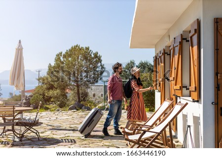 Young couple arriving to at holiday home   Royalty-Free Stock Photo #1663446190