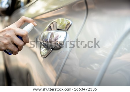 Hand of woman is spraying alcohol,disinfectant spray on handle of car door,safety,prevent infection of Covid-19 virus,contamination of germs or bacteria,wipe clean surfaces that are frequently touched #1663472335