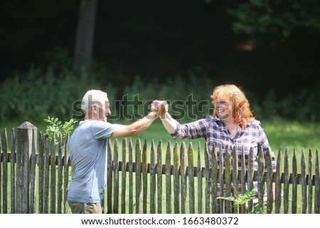 Neighbors greeting each other over fence #1663480372