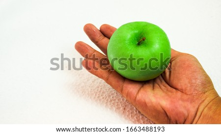 Green apple on man's hand isolated on white surface background. Fresh picture for healthy lifestyle concept.