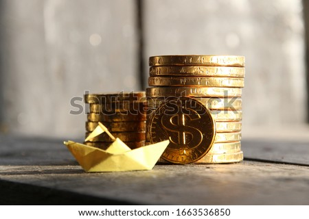 startup concept, graph of gold coins and a paper boat