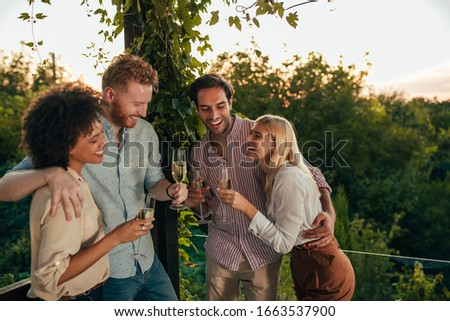 Two couples celebrating with drinks at the terrace party #1663537900
